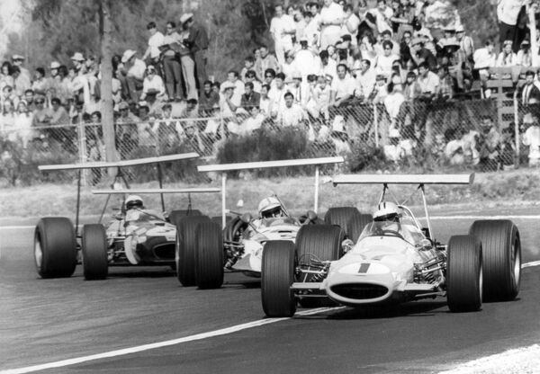 1968 Mexican Grand Prix. Mexico City, Mexico. 3 November 1968. Denny Hulme, McLaren M7A-Ford, retired, leads John Surtees, Honda RA301, retired, and Jack Brabham, Brabham BT26-Repco, 10th position, action. World Copyright: LAT Photographic Ref