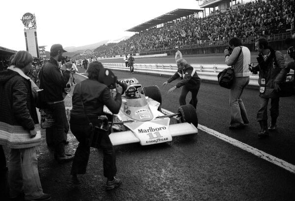 Formula One World Championship: At the end of the race Teddy Mayer, McLaren Team Manager, centre, attempts to slow down James Hunt, McLaren M23