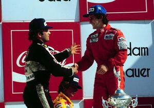 Elio de Angelis congratulates race winner Alain Prost on the podium